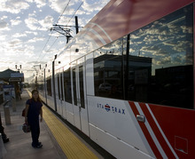 Tribune File Photo A passenger waits to catch an early morning TRAX train. The Utah Transit Authority is looking to end the free fare zone in downtown Salt Lake City -- starting with buses soon and, in a few years, TRAX.