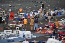 A crowd gathers around debris after a P-51 Mustang airplane crashed at the Reno Air show on Friday, Sept. 16, 2011 in Reno Nev.. The plane plunged into the stands at the event in what an official described as a