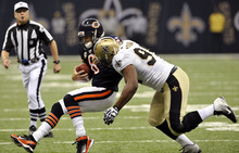 Chicago Bears quarterback Jay Cutler (6) tries to elude a tackle by New Orleans Saints defensive end Cameron Jordan (94) during the first half of an NFL football game at the Louisiana Superdome in New Orleans, Sunday, Sept. 18, 2011. (AP Photo/Bill Feig)