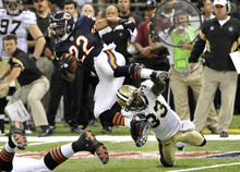 Chicago Bears running back Matt Forte (22) is tripped by New Orleans Saints cornerback Jabari Greer (33) during the first quarter of an NFL football game at the Louisiana Superdome in New Orleans, Sunday, Sept. 18, 2011. (AP Photo/Bill Feig)