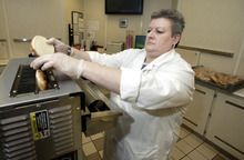 In this Sept. 15, 2011 photo, Liz Shires, Wendy's research and development laboratory coordinator, toasts two buns for the new Dave's Hot 'N Juicy Cheeseburger in the lab at the company's international headquarters in Dublin, Ohio. (AP Photo/Paul Vernon)