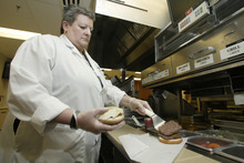 In this Sept. 15, 2011 photo, Liz Shires, Wendy's research and development laboratory coordinator, works on assembling one of the new Dave's Hot 'N Juicy Cheeseburgers in the lab at the company's international headquarters in Dublin, Ohio. (AP Photo/Paul Vernon)