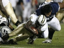 Trent Nelson  |  The Salt Lake Tribune After losing his helmet, BYU's Travis Tuiloma sacks Central Florida quarterback Jeff Godfrey. BYU vs. Central Florida, college football at LaVell Edwards Stadium in Provo, Utah, Friday, September 23, 2011.