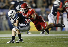 Trent Nelson | The Salt Lake Tribune  Utes defensive back Reggie Topps (28) tackles BYU wide receiver JD Falslev (12) during BYU's game against Utah at Lavell Edwards Stadium in Provo, Utah September 17, 2011.