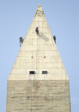 A team of engineers, from left, Dan Gach, Emma Cardini, center, and Katie Francis, harnessed to ropes , inspect the exterior of the Washington Monument for damage caused by last month's earthquake, Wednesday, Sept. 28, 2011, in Washington.  (AP Photo/Evan Vucci)