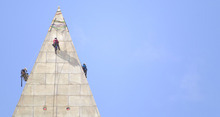A team of engineers, from left, Dan Gach, Emma Cardini, center, and Katie Francis, harnessed to ropes , inspect the exterior of the Washington Monument for damage caused by last months earthquake, Wednesday, Sept. 28, 2011, in Washington.  (AP Photo/Evan Vucci)