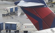 Delta baggage handlers service a plane at a boarding gate at Detroit Metropolitan Airport. Carlos Osorio    The Associated Press