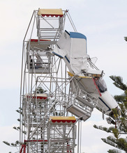 Two men and their ultra-light plane hang from a Ferris wheel while two children sit in a carriage near the top of the ride at a country festival at Old Bar, Australia, Saturday, Oct. 1, 2011. The four people were trapped in the tangled wreckage for hours after the plane crashed into the ride. (AP Photo/Carl Muxlow)