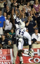 Rick Egan  | The Salt Lake Tribune   Utah State Aggies cornerback Jumanne Robertson (13) hits Brigham Young Cougars wide receiver Cody Hoffman, but Hoffman holds onto the ball for a BYU Touchdown, in football action, BYU vs. Utah State, in Provo, Friday, September 30, 2011.