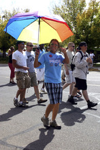 Lisa J. Church for The Tribune   Moab resident Marcy Clokey-Till carries a rainbow umbrella as she marches through Moab's downtown in support of equal rights during Moab's first gay pride parade and festival.