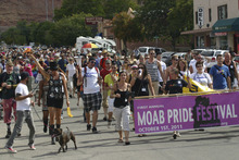 Lisa J. Church for The Tribune Moab Pride Festival founders Amy Stocks, left holding sign, and Ali Lingel, center holding sign, lead a group of more than 300 people through downtown Moab during the town's first gay pride parade.
