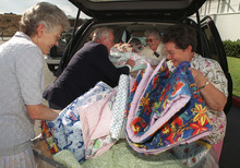 Besides attending church, Mormons also perform humanitarian outreach. Here, service missionaries unload donated quilts, which will be sent to Kosovo refugees.