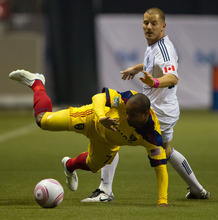 Real Salt Lake's Andy Williams, left, is tripped by Vancouver Whitecaps' Jordan Harvey during first-half MLS soccer game action in Vancouver, British Columbia, on Thursday, Oct. 6, 2011. (AP Photo/The Canadian Press, Darryl Dyck)