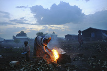 A Congolese woman, displaced from a surrounding village, cooks with a fire inside Kibati camp in Goma, North Kivu province, Democratic Republic of the Congo. Courtesy of Lynsey Addario/VII Network/Corbis