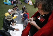 Scott Sommerdorf     The Salt Lake Tribune              Occupy SLC camper Matt Gassner sends a text message on his cellphone during a meeting of Occupy SLC members in their growing tent city in Pioneer Park, Monday, October 10, 2011.