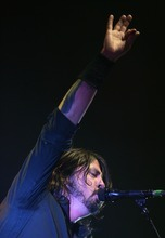 Steve Griffin  |  The Salt Lake Tribune   Foo Fighters lead vocalist Dave Grohl holds his hand in the air as he sings during the first song of a concert at the Maverik Center in West Valley City on Tuesday, Oct. 11, 2011.