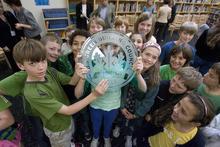 Paul Fraughton | The Salt Lake Tribune Students at The McGillis School in Salt Lake City hold up a plaque Friday, Oct. 14, given to the school by the U.S. Green Building Council. The McGillis School was awarded a  Gold LEED certificate for its green building practices employed in the expansion of the school building.