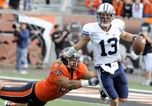 Greg Wahl-Stephens  |  The Associated Press  Oregon State's Andrew Seumalo, left,misses a tackle against BYU's quarterback Nelson Riley (13) during the first half of an NCAA college football game in Corvallis, Ore., Saturday.