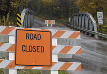 A road closed sign leading into the Muskingum County Animal Farm is shown Wednesday, Oct. 19, 2011, in Zanesville, Ohio. Police with assault rifles stalked a mountain lion, grizzly bear and monkey still on the loose after authorities said their owner apparently freed dozens of wild animals and then killed himself. (AP Photo/Tony Dejak)