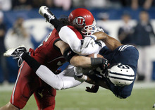 BYU wide receiver Ross Apo, right, is upended by Utah linebacker Chaz Walker, left, after catching a 7-yard Jake Heaps pass during the second half of an NCAA college football game, Saturday, Sept. 17, 2011, at LaVell Edwards Stadium in Provo, Utah. Utah defeated BYU 54-10. Officials ruled the pass complete. (AP Photo/Colin E Braley)