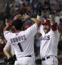Texas Rangers' Mike Napoli, right, celebrates with Yorvit Torrealba (8) and Elvis Andrus (1) after hitting a three-run home run during the sixth inning of Game 4 of baseball's World Series against the St. Louis Cardinals Sunday, Oct. 23, 2011, in Arlington, Texas. (AP Photo/Charlie Riedel)