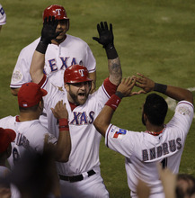 Texas Rangers' Mike Napoli celebrates with Yorvit Torrealba (8) and Elvis Andrus (1) after hitting a three-run home run during the sixth inning of Game 4 of baseball's World Series against the St. Louis Cardinals Sunday, Oct. 23, 2011, in Arlington, Texas. (AP Photo/Paul Sancya)