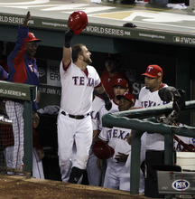 Texas Rangers' Mike Napoli comes out of the dugout to acknowledge the fans after hitting a three-run home run during the sixth inning of Game 4 of baseball's World Series against the St. Louis Cardinals Sunday, Oct. 23, 2011, in Arlington, Texas. (AP Photo/Tony Gutierrez)
