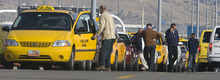 Al Hartmann  |  The Salt Lake Tribune Taxi cab drivers wait for fares south of the Salt Lake City International Airport on Thursday. Two local cab companies were passed over for contracting for on-demand services to two out-of-state firms.