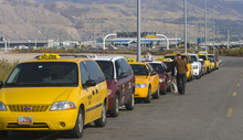 Al Hartmann  |  The Salt Lake Tribune Taxi cab drivers que up for fares south of the Salt Lake International Airport on Thursday October 27. Two  local cab companies were passed over for contracting for on-demand services to two out-of-state firms.