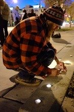 Trent Nelson  |  The Salt Lake Tribune Braden Jordan lights candles in front of the Public Safety Building in Salt Lake City on Wednesday, Oct. 26, 2011. About two dozen protesters with Occupy Salt Lake marched from Pioneer Park to the Public Safety Building. They lit candles to show appreciation for the Salt Lake City police, but to protest the actions of the police in Oakland, Calif.