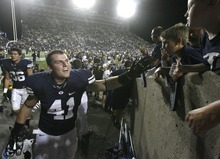 Rick Egan  | The Salt Lake Tribune   Brigham Young Cougars running back Austin Heder (41) high-fives kids as he runs to the locker room after the Cougars last second victory over the Aggies, at Lavell Edwards Stadium in Provo on Sept. 30. Heder is doubtful against TCU on Friday because of a nasty shoulder stinger he suffered against Idaho State on Saturday.