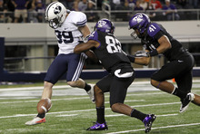 BYU kicker Riley Stephenson (99) tries to kick the ball after missing the snap as TCU's Josh Boyce (82) and Jonathan Anderson (41) close in during the first half of an NCAA college football game at Cowboys Stadium Friday, Oct. 28, 2011, in Arlington, Texas. (AP Photo/LM Otero)