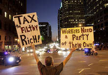 Occupy Los Angeles protester Alvaro Maldonado, 59, holds signs during a rally in Los Angeles, Wednesday, Nov. 2, 2011. In Los Angeles, New York and other cities, demonstrators held their own rallies in solidarity with the Oakland protesters, who called for Wednesday's
