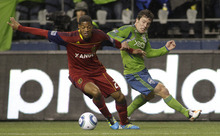 Real Salt Lake's Chris Schuler, left, fends off Seattle Sounders' Mike Fucito during the first half of an MLS playoff soccer match Wednesday, Nov. 2, 2011, in Seattle. (AP Photo/Ted S. Warren)