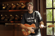 In this Aug. 16, 2011 photo, Vince Gill is shown with some of his Grammy awards at his home in Nashville, Tenn. (AP Photo/Mark Humphrey)
