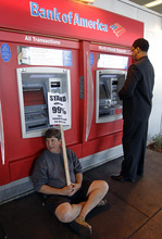 In this Nov. 2, 2011 file photo, a protesters sits in front of an ATM machine as a customer gets money at a Bank of America branch in Oakland, Calif. The spirit behind