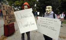 In this Friday, Oct. 21, 2011 photo, Papi Chulo, left, and Brian Xaivier, both of Ravena, N.Y., wear Guy Fawkes masks while supporting the Occupy Wall Street movement in Albany, N.Y. From New York to San Francisco to London, some of the demonstrators decrying a variety of society's ills are sporting stylized masks loosely modeled on a 17th-century English terrorist, whether they know it or not. The masks come from