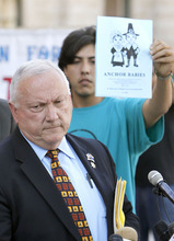 Ross D. Franklin  |  The Associated Press Arizona state Sen. Russell Pearce, R-Mesa, left, talks Tuesday about efforts by state legislators to propose legislation to deny U.S. citizenship to children of illegal immigrants. Protester Abraham Venzor-Hernandez, of the Puente movement, which works for fairness in immigration reform, stands in the background.
