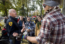 Al Hartmann  |  The Salt Lake Tribune Salt Lake City Police Chief Chris Burbank, left,  reasons with members of the Occupy Salt Lake in Pioneer Park Friday afternoon November 11.  He announced to occupiers that the camp would have to be dismantled and vacated by sundown on Saturday due to a death in the camp earlier on Friday morning and public safety concerns.