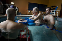 Steve Griffin  |  The Salt Lake Tribune   Brooke Hopkins, who was paralyzed from a bicycle accident three years ago, struggles to complete an exercise as he works with physical therapist Matt Hansen, left, and LMT/PT Aide Mike Erickson during pool therapy at Neuroworx in South Jordan, Utah Friday, November 11, 2011.