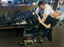 Steve Griffin  |  The Salt Lake Tribune   Mike Erickson, a massage therapist and physical therapist aide, helps Brooke Hopkins, who was paralyzed from a bicycle accident three years ago, into his electric chair during therapy at Neuroworx in South Jordan, Utah Friday, November 11, 2011.