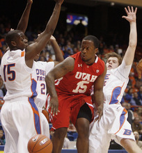 Utah guard Josh Watkins, center, slices between Boise State defenders, including Thomas Bropleh, left, during the first half of an NCAA college basketball game on Wednesday, Nov. 16, 2011, in Boise, Idaho. (AP Photo/Joe Jaszewski)