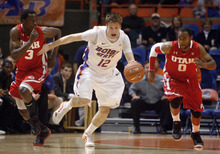 Boise State's Igor Hadziomerovic (12) dribbles away from Utah's Anthony Odunsi (3) and Chris Hines (0) during the first half of an NCAA college basketball game Wednesday, Nov. 16, 2011 in Boise, Idaho. (AP Photo/Joe Jaszewski)