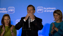 Conservative Popular Party candidate Mariano Rajoy reacts next to his wife Elvira Fernandez Balboa, left, and the secretary general of the party Maria Dolores de Cospedal, right, as they celebrate after wining in the national election polls at the party headquarter in Madrid, Spain, Sunday, Nov. 20, 2011. (AP Photo/Emilio Morenatti)