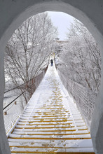 In this Sunday Nov. 20, 2011 photo, a tourist walks on a bridge after a snow in the Greater Hinggan Mountains in Hulunbuir City, in northern China's Inner Mongolia Region. (AP Photo) CHINA OUT