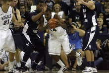 Chris Detrick  |  The Salt Lake Tribune Utah State Aggies forward Kyisean Reed (34) is guarded by Brigham Young Cougars forward Brandon Davies (0) and Brigham Young Cougars forward Noah Hartsock (34) during the first half of the game at the Dee Glen Smith Spectrum Friday November 11, 2011. Utah State won the game 69-62.