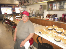 Salt Flats Cafe owner Marcelo Escobedo sits on the counter at the Salt Flats Cafe east of Wendover. (Tom Wharton Photo).