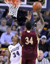 Denver forward Chris Udofia takes a shot as Utah State forward Kyisean Reed defends during an NCAA college basketball game Wednesday, Nov. 30, 2011, in Logan, Utah. (AP Photo/The Herald Journal, Eli Lucero)