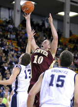 Denver forward Rob Lewis (10) takes a shot over Utah State guard Preston Medlin (13) and as forward Mitch Bruneel watches during an NCAA college basketball game Wednesday, Nov. 30, 2011, in Logan, Utah. (AP Photo/The Herald Journal, Eli Lucero)