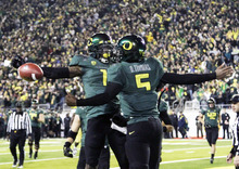 Oregon quarterback Darron Thomas, right, celebrates with teammate Josh Huff after Thomas scored a rushing touchdown against UCLA during the first half of their NCAA Pac-12 Championship NCAA college football game in Eugene, Ore., Friday, Dec. 2, 2011.(AP Photo/Don Ryan)